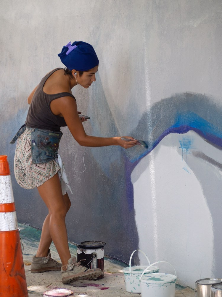 Cat Ferraz painting a mural in Hollywood, Fla.