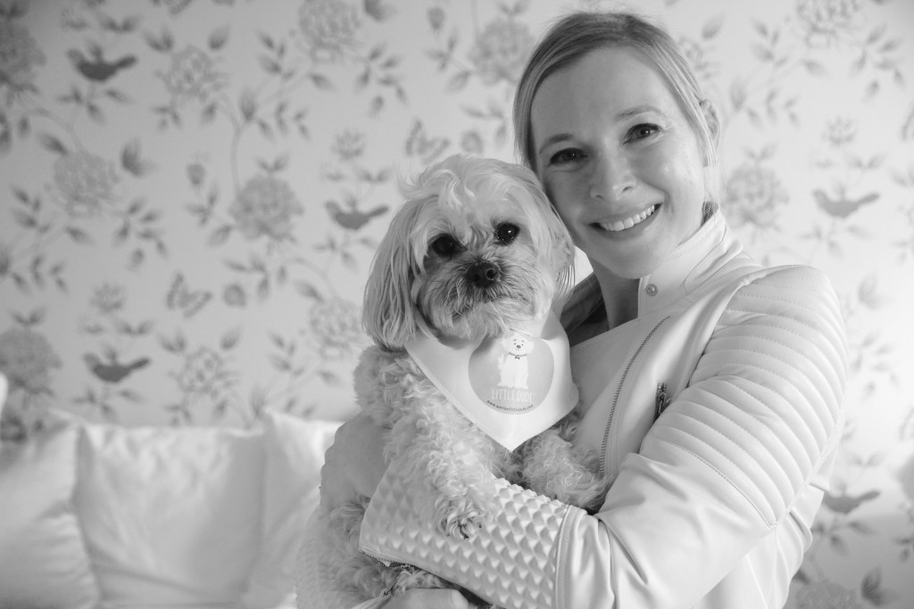Black and white photo of Cara Zelas and her therapy dog Little Dude.