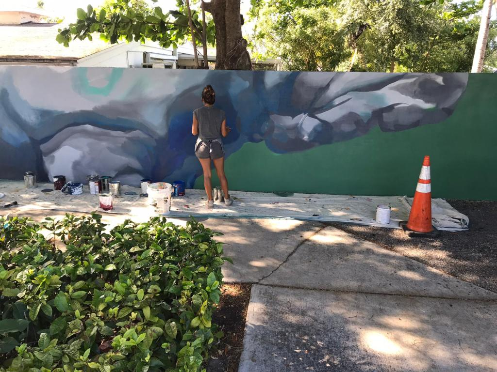 Cat Ferraz paining a mural in Hollywood Fla, on a concrete sound barrier.