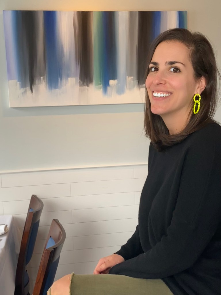Photo of Amanda Arbeter in front of one of her abstract paintings.