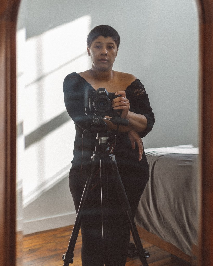Brittanny Taylor posing with her camera taking a self-portrait.