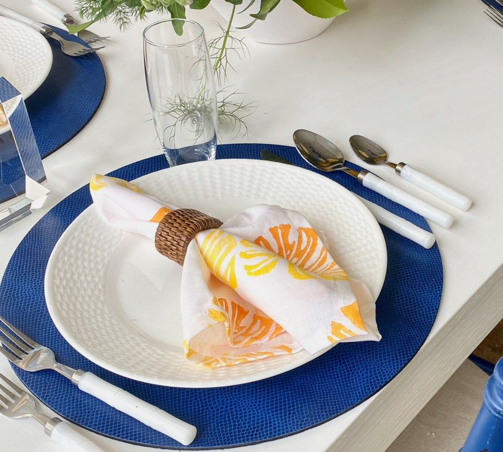 A place setting with a cloth napkin printed with one of Tulusa's designs.