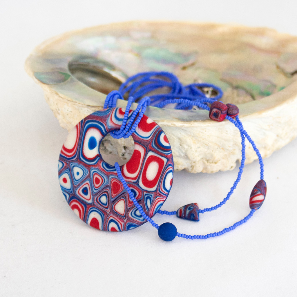 One of Yuliya Shulman's pieces of handmade jewelry in red, white and blue. Polymer clay and seed beads.