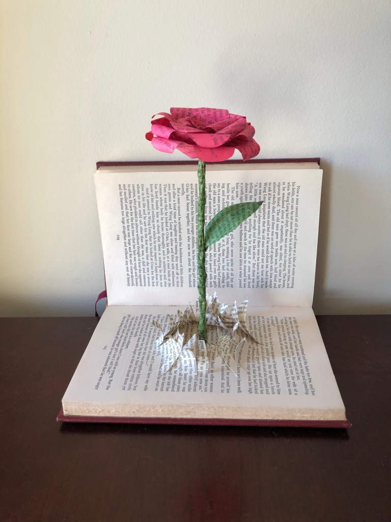 In this paper art, a rose, created from the pages of the same damaged book, appears to have burst through the publication.