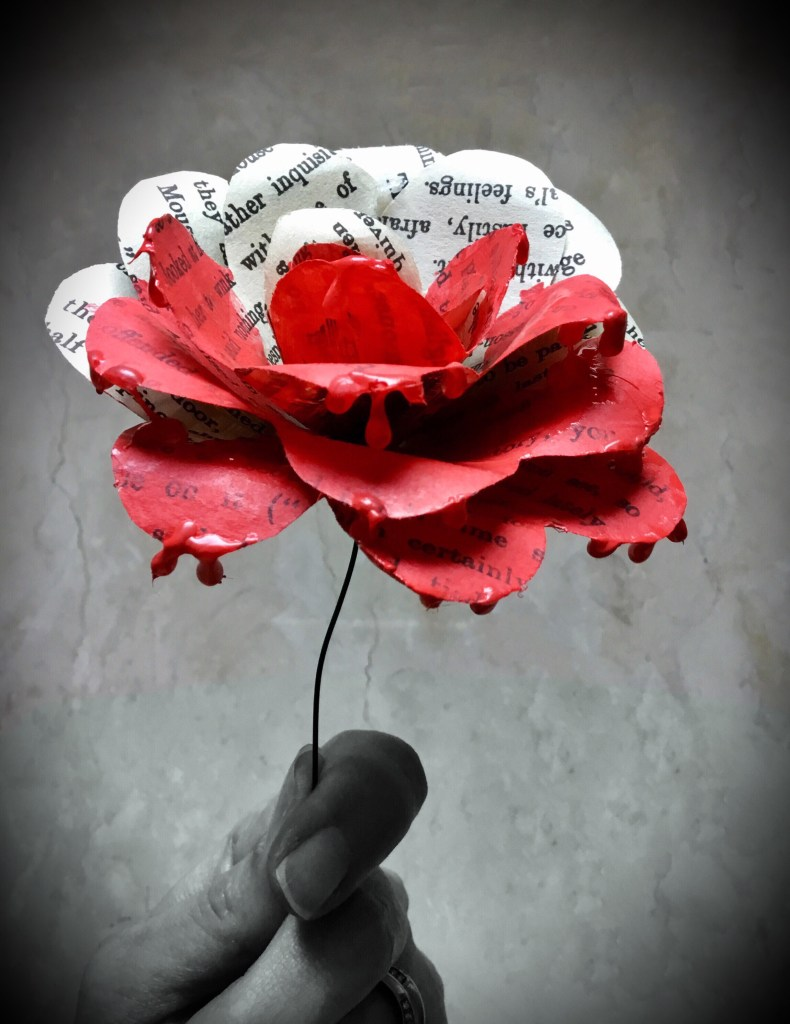 A photo of a paper flower made from book pages. It is red on one half and black and white on the other.