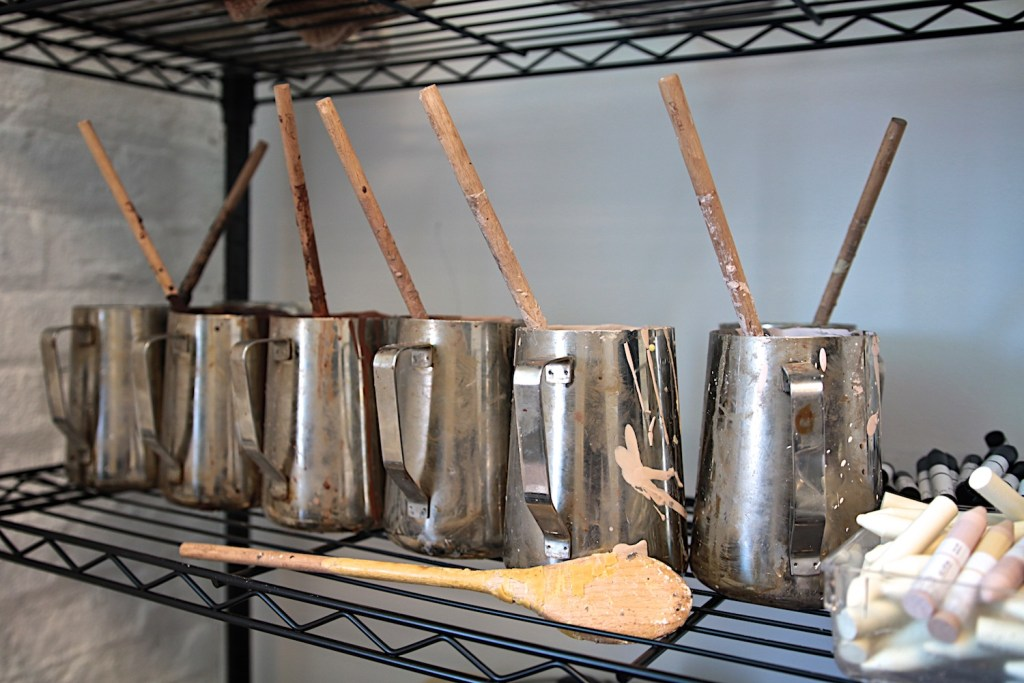 Image showing 6 stainless steel pitchers filled with different colors of melted wax that Sabine uses to mold crayons.